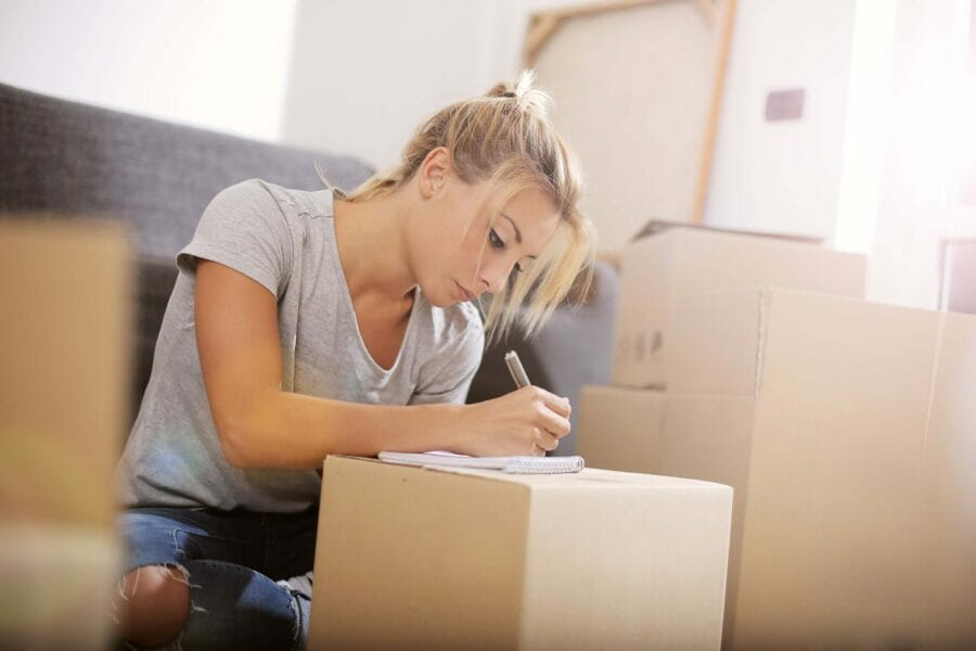 Young woman writing on box